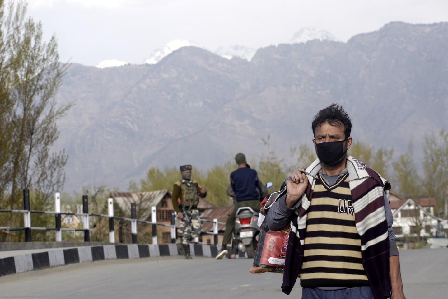 Kashmiri man wearing face mask with soldiers in the background