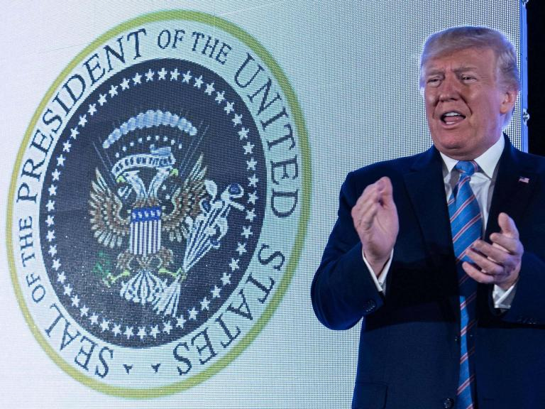 Trump speaks in front of fake presidential seal mysteriously manipulated to feature Russian eagles and golf clubs