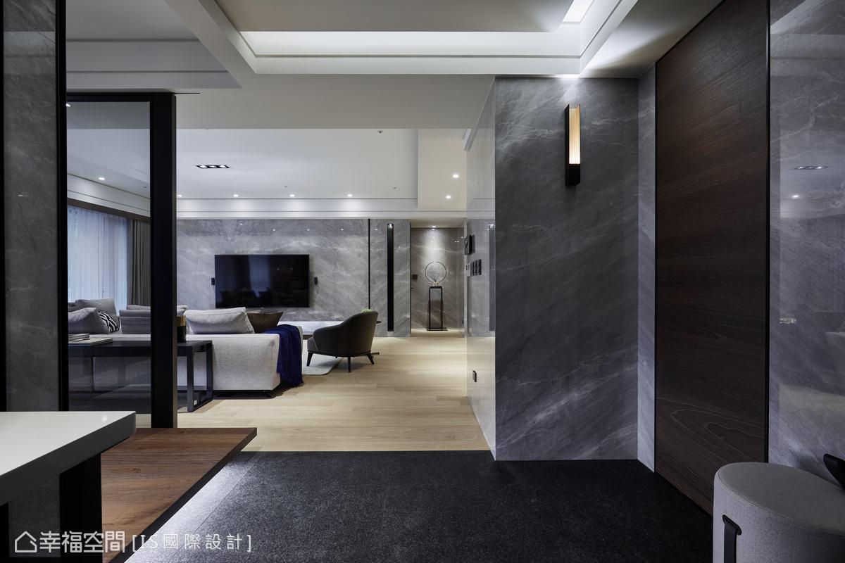 自玄關向左進入客廳,採用連續性石材一氣呵成的鋪敘客廳立面,並在廊道盡頭處擺放藝品,型塑端景視覺。