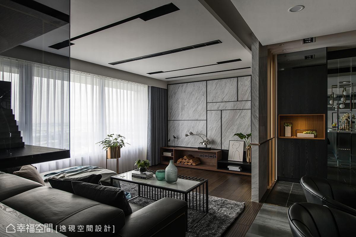 客廳的電視主牆以淺灰色銀狐大理石營造空間奢華質感,並透過黑色鐵件在牆面上做了幾何比例切割,俐落線條讓牆面更添時尚感。