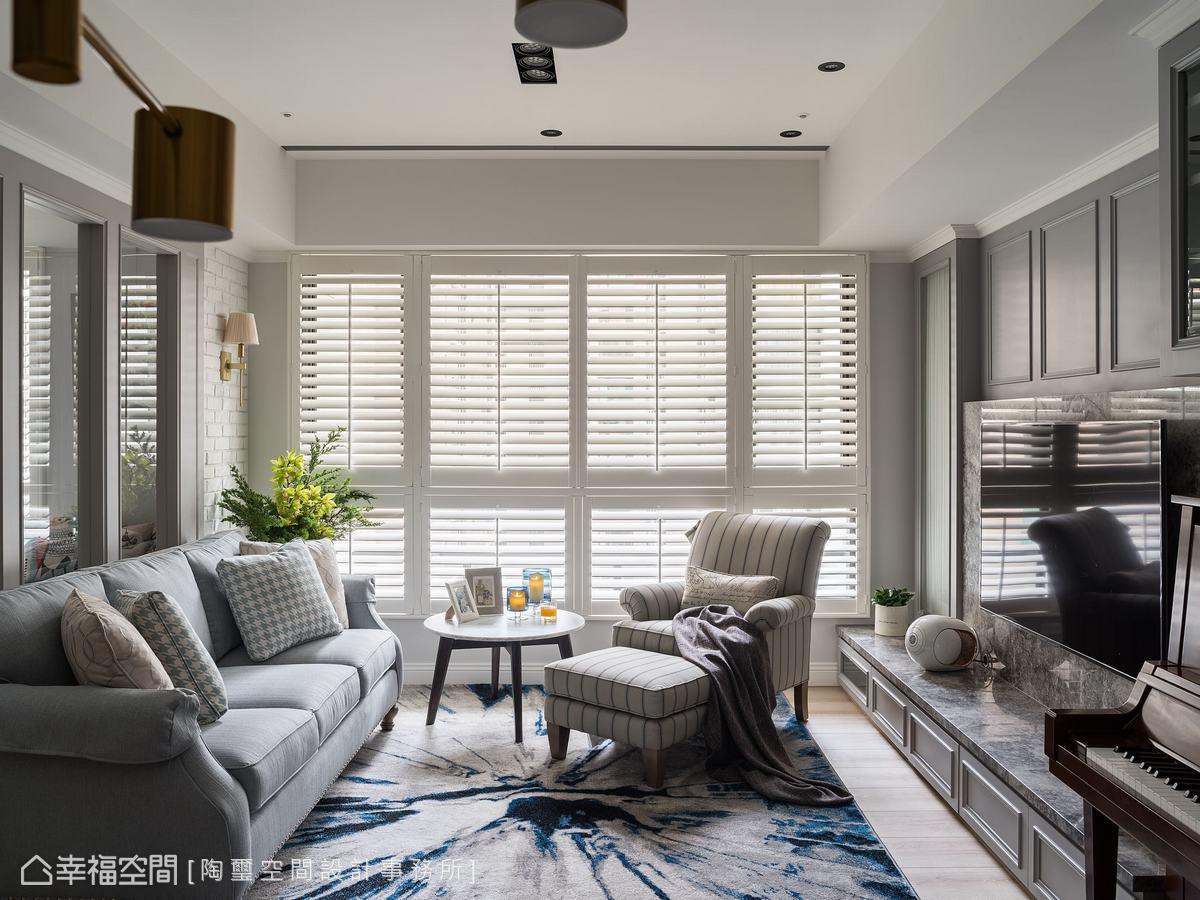 藍灰色的線板與白色百葉窗,交織出溫馨居家氛圍。藍色布沙發與白色條紋單人沙發椅,則勾勒出柔軟的空間情調。