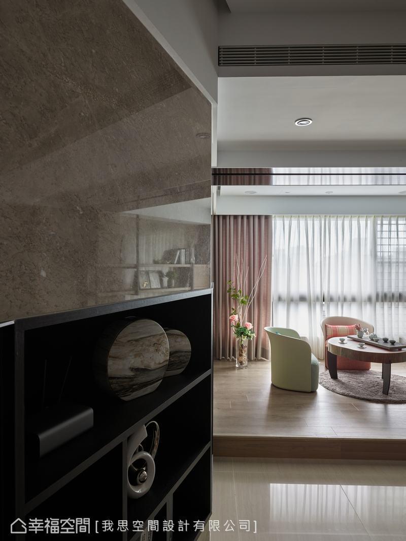電視牆斜角處設置木框層板,展示屋主的收藏品,水平線條加強牆面的延展性,異材質搭配展現空間休閒感。