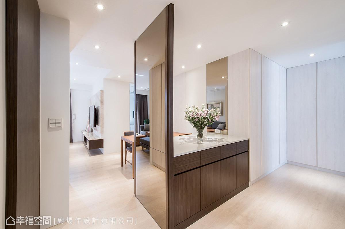 柱體和立面間的畸零地,規劃雙面式備餐櫃,並鑲貼鏡面做為整衣鏡。在進入廚房的轉角走道,還增加大型L櫃做收納空間。