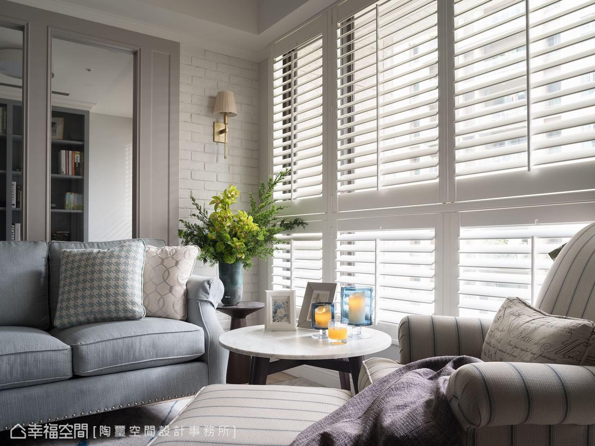 沙發背牆的一側,鋪陳了文化石增加層次感,隨著木百葉窗篩下的光影變化,隨興坐在客廳一角就是生活的日常。