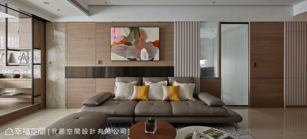 牆面從客廳延伸至廚房,並以木皮、鍍鈦金屬、格柵、玻璃等四種不同材質和造型穿插,增加變化性。