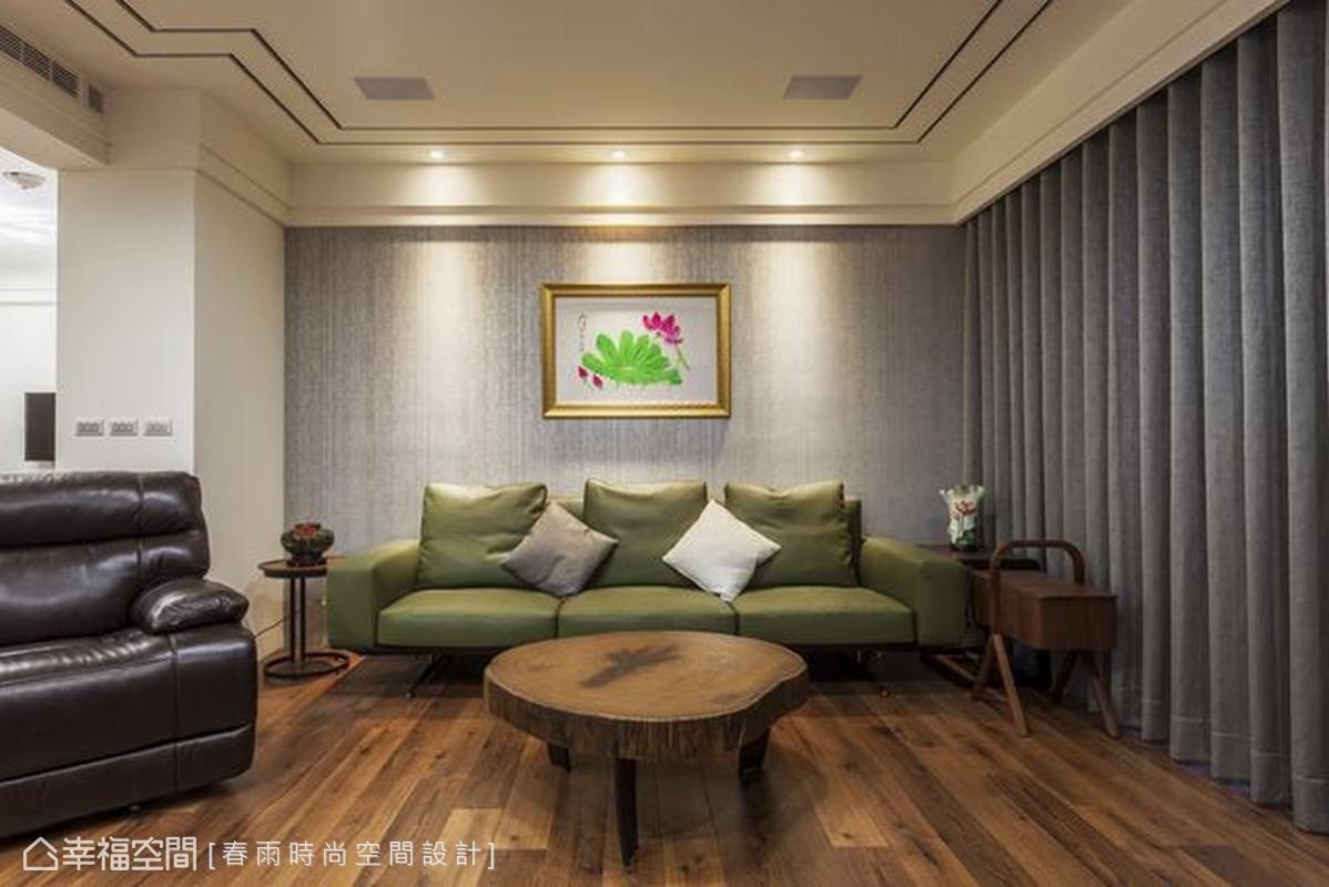 橄欖綠的沙發在原木色的客廳區,襯托出和諧的自然感,沙發背牆採用壁紙提升質感,天花板塑造簡約的線條,搭配窗簾柔軟的皺摺,豐富整體視覺層次。
