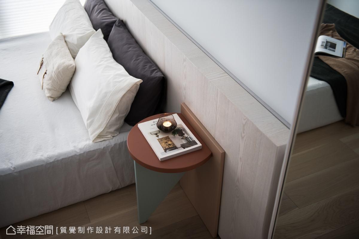 床頭背牆以鋼刷木皮鋪陳,搭配幾何圖形組成的床頭櫃既簡約又具獨特設計感。