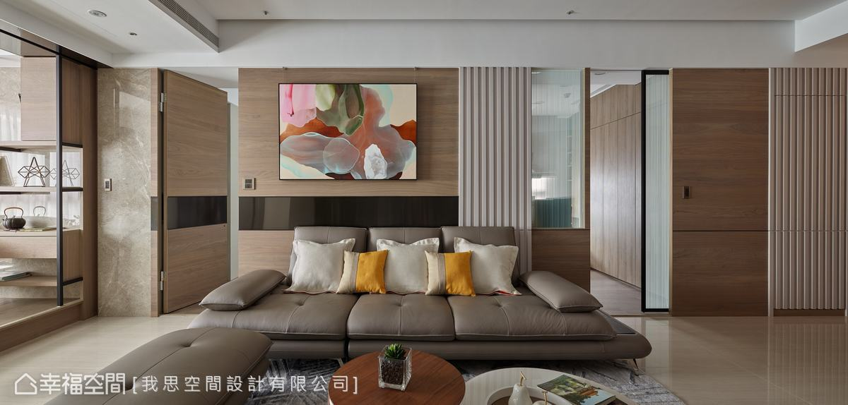 沙發背牆後方為私領域,設計師整合空間機能,以隱藏門連接,維持場域的調性平衡。