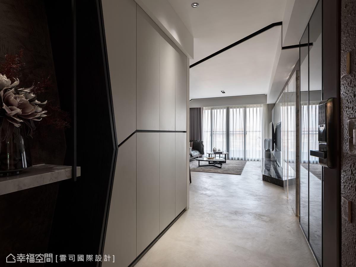 天花板的燈帶及線條設計,與玄關櫃體的門板線條呼應,讓視覺感更開闊。