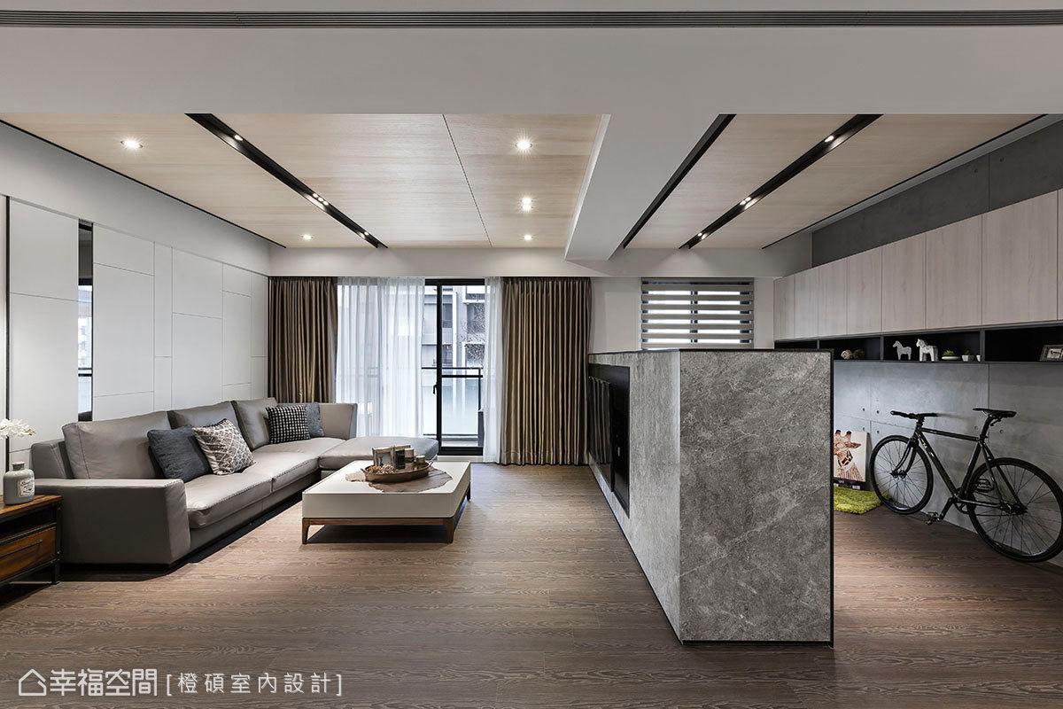 半高電視牆後方規劃成書房,以流暢動線與客廳緊密相連;沙發牆使用溝縫形成幾何切割造型,鑲貼灰鏡讓層次感躍然眼前。