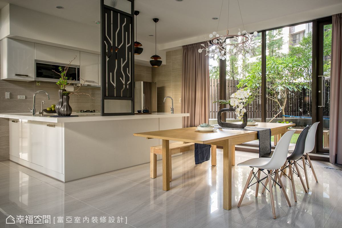 富亞室內裝修設計規劃八人的餐桌,讓親朋好友都能相聚於此,餐吧空間同樣用鏤空意象的屏風,巧妙化解開門見灶的風水顧慮。