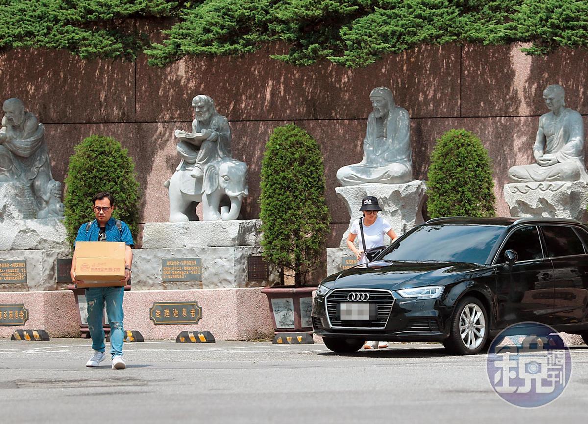 10:06 謝忻的車停在金山的蓬萊陵園,百是傳播製作人先行搬著一箱金紙走在前面,謝忻(右)則戴著漁夫帽下車。