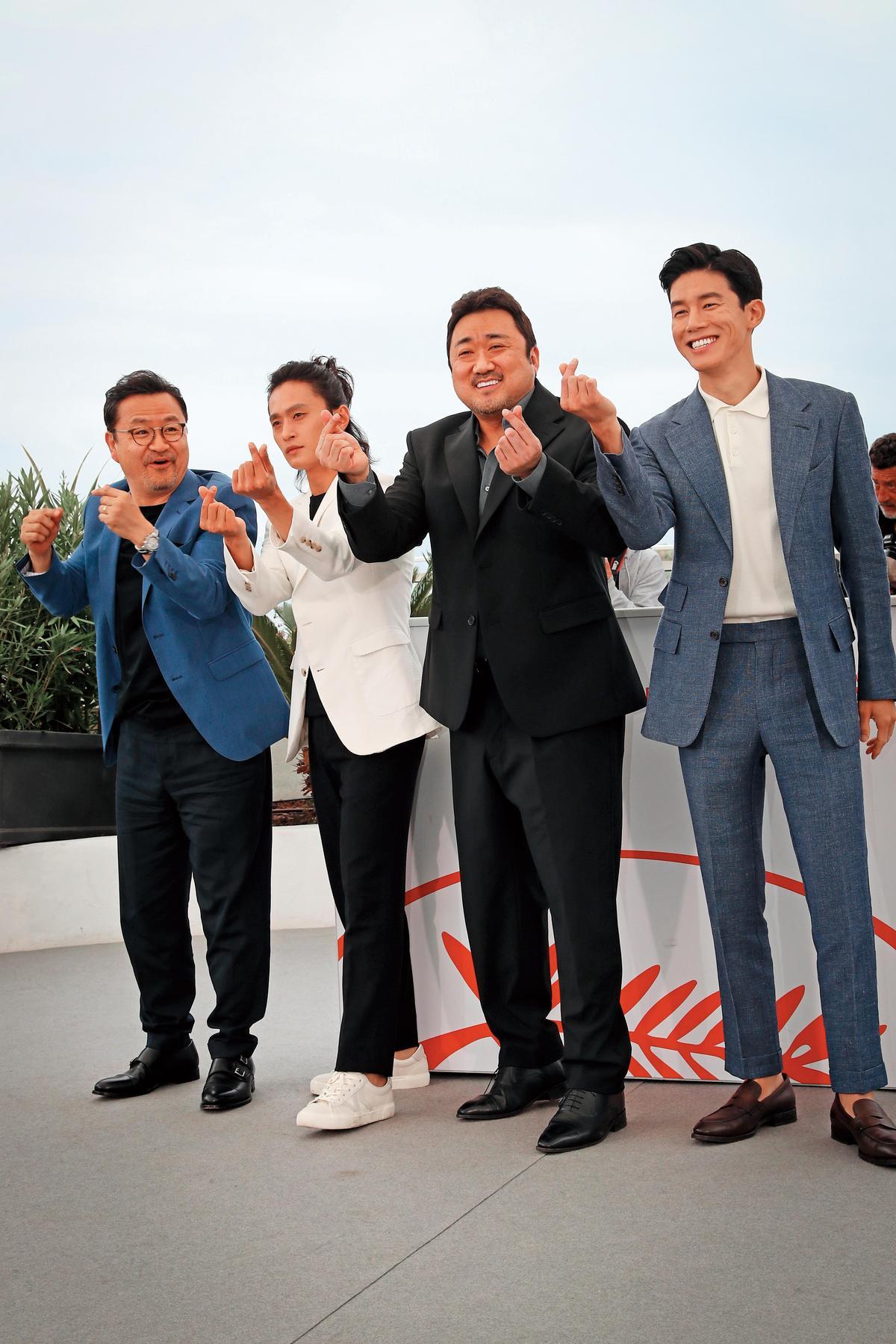 《極惡對決》在本屆坎城影展午夜放映單元受到觀眾歡迎,導演李元泰(左起)率演員金成圭、馬東石與金武烈比手指愛心。(東方IC)