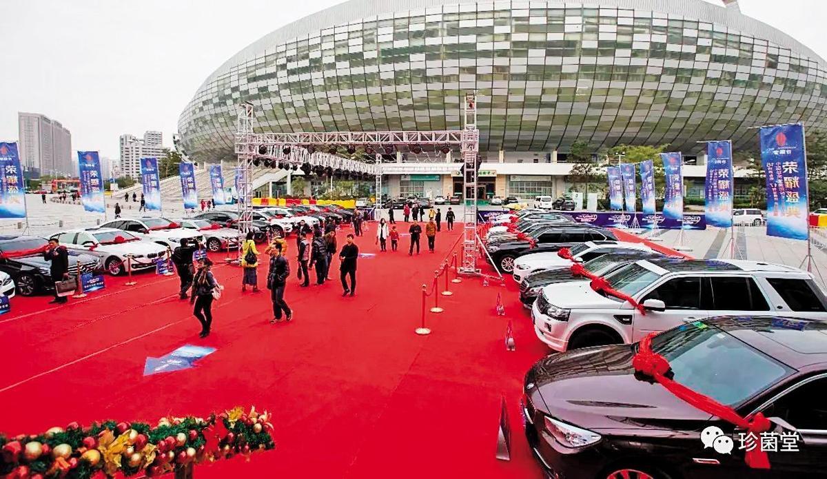 珍菌堂在中國舉辦晚會的場館外停滿各式名車,公司強調是要贈送給績效卓著的培植戶。(翻攝自百度)