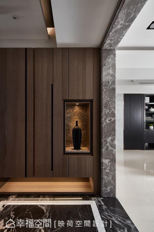 玄關以自然流水紋路的大理石地坪,搭配鞋櫃木皮的俐落線條設計,形塑一進門的恢宏氣勢及質感,也揭開公共空間的大器尺度氛圍。