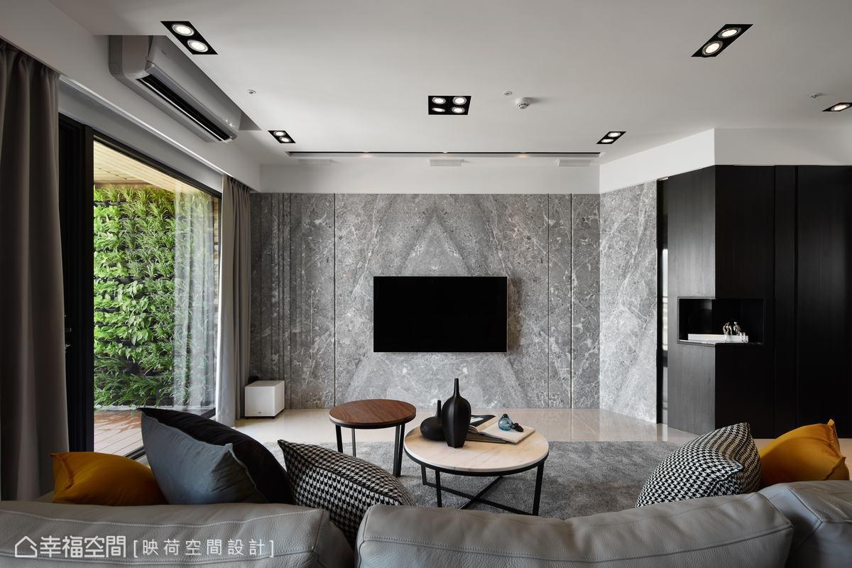 客廳電視主牆以雲多拉灰大理石紋路鋪陳出山水流動的視覺效果,也與陽台植生牆相呼應,並與儲藏間兼機房的櫃體以鍍鈦材質收邊,提升空間質感。