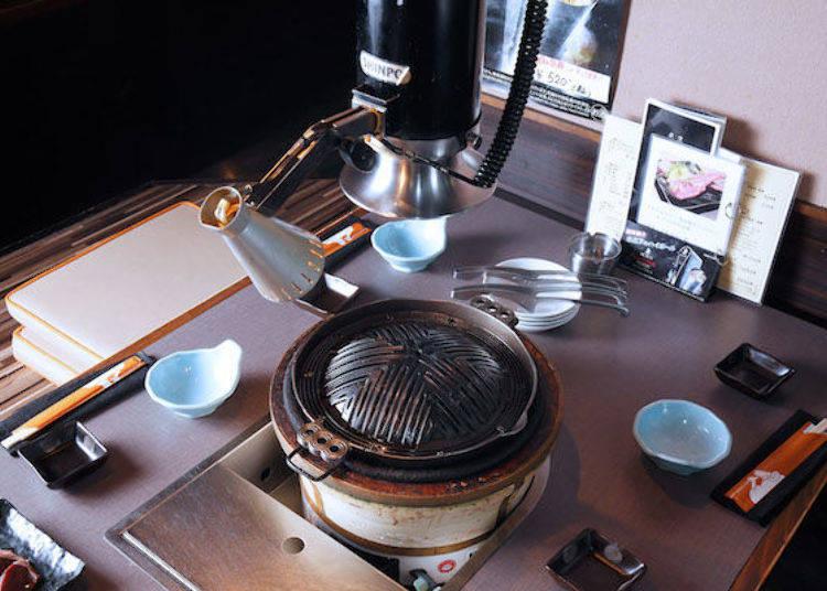 成吉思汗蒙古烤肉的鐵盤上有設置排煙管。左上方的燈是為了加強手邊的亮度。