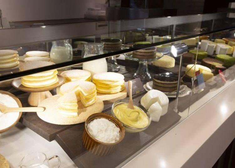 擺設於展示櫃中的蛋糕與商品樣品。前方中央為慶祝LeTAO 20週年的紀念甜點「乳酪卡士達奶油蛋糕(ル コッタ)」(1個1,944日圓)。