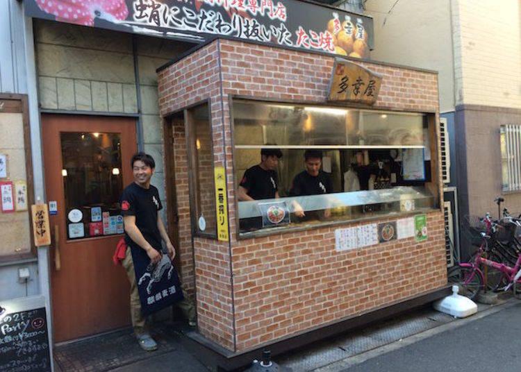 ▲餐廳招牌上寫著「注重章魚品質的精選章魚燒」,入口左側的樓梯上方則是包場專用區域(8~20人)。提供僅限3000日圓起的套餐(需要預約)