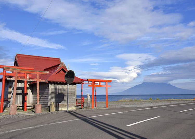 佇立在沿岸的「見內神社」。鮮豔的朱色與天空藍的強烈對比顯得格外美麗!後方遠遠望去就是利尻山。