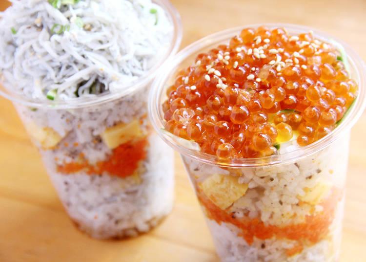 裝滿清燙吻仔魚和醬油醃漬鮭魚卵的杯裝壽司,看起來就像千層派一樣。左為吻仔魚,右邊則是鮭魚卵,各810日圓。
