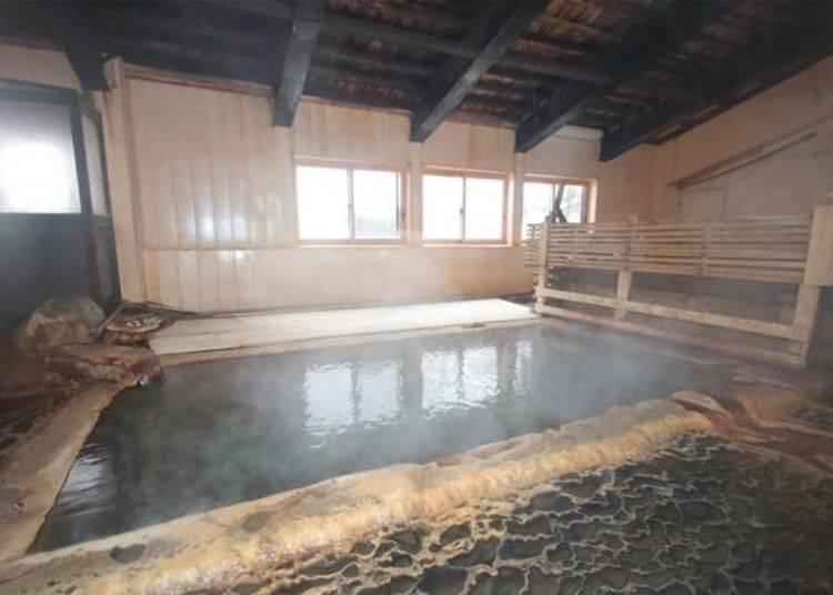 位於後方的室內湯。溫泉的溫度微燙約42度。右後側柵欄的後面還有兩處小型木製湯池。