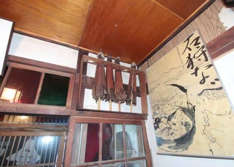 玄關裝飾著年代久遠的油紙傘與畫報。