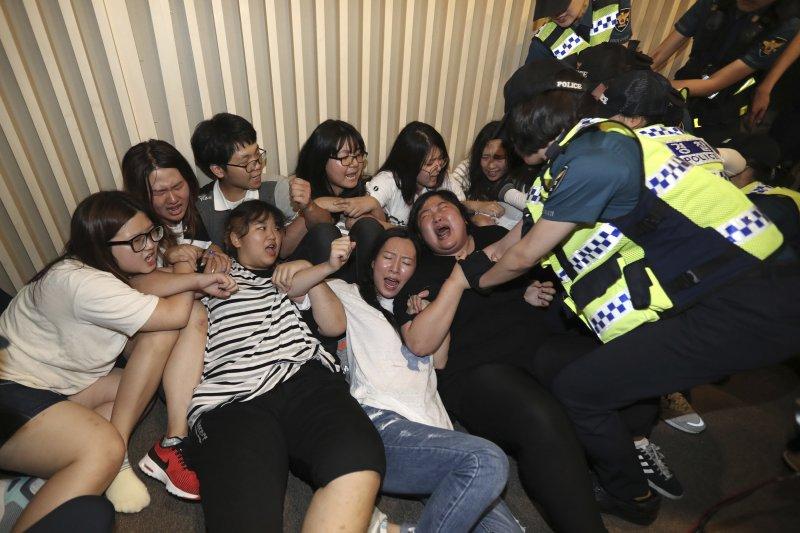 南韓大學生28日闖入慰安婦支援財團「和解‧平癒財團」的成立會場抗議。(美聯社)