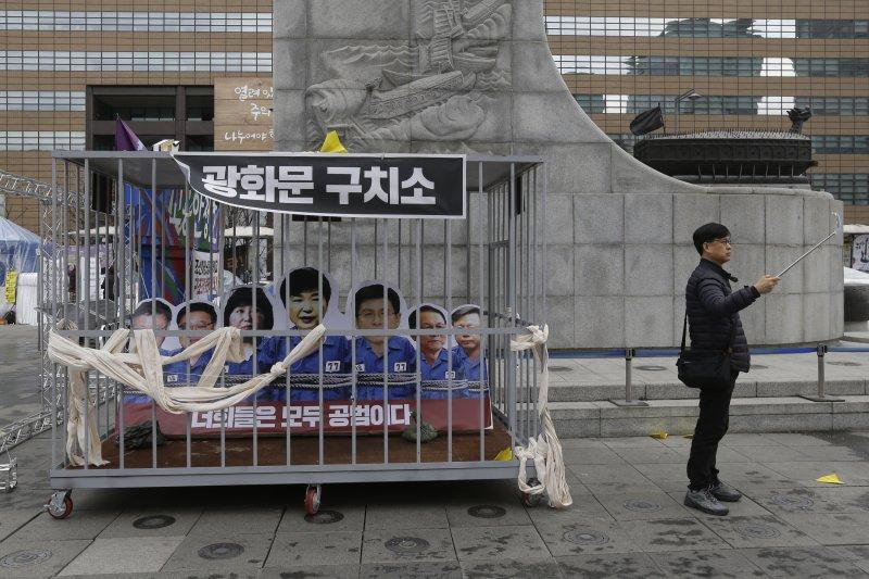 一位南韓民眾在首爾街頭與抗議朴槿惠的裝置作品合拍,朴槿惠與「親信門」的相關嫌犯均被「打入大牢」。(美聯社)