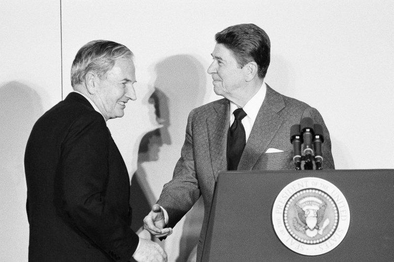 大衛.洛克斐勒(左)與美國前總統雷根握手(AP)