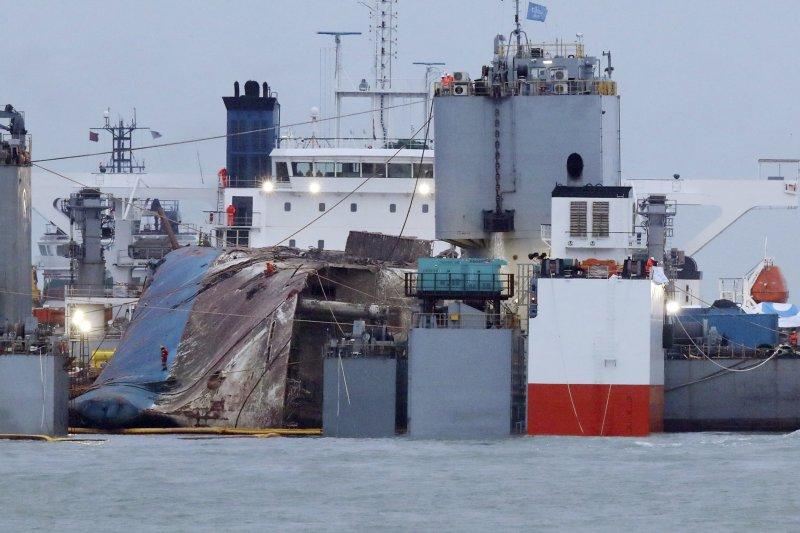 2014年4月16日發生沉船慘劇的南韓渡輪世越號(Sewol),25日被抬至半潛船上,打撈作業基本成功。(AP)